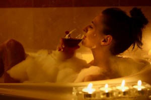 candle lit bath with glass of wine