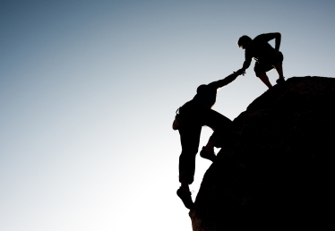 one man helping another up a mountain in silhouett