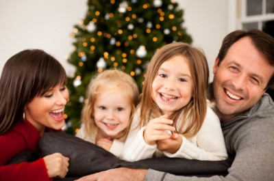 A family at Christmas time in front of Christmas tree
